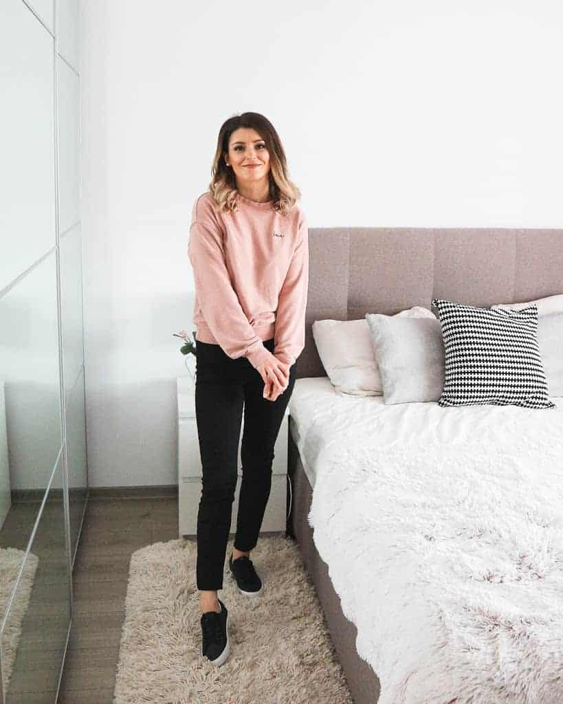 pink sweatshirt, black jeans and black trainers outfit