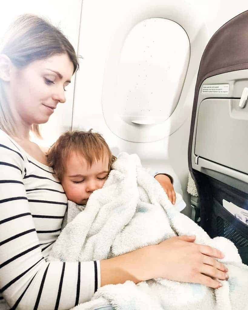 mother and toddler sleeping on a plane