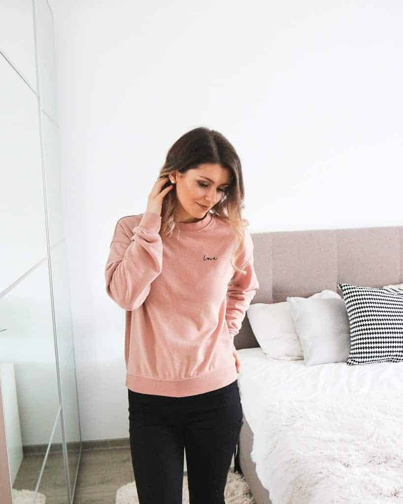 H&M pink love jumper with black pants and black trainers outfit