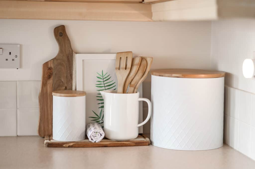 minimalist countertop with wooden spatulas, serving boards and white canisters
